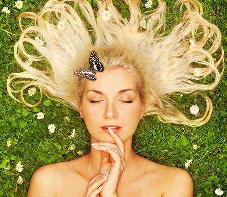 lying in grass: Mujer joven con una mariposa   Foto de archivo