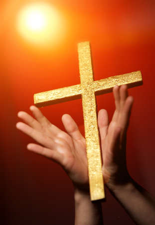 Golden cross in human hands photo
