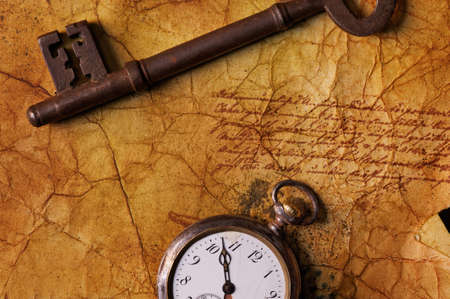 The old key with a clock on the textured paper Stock Photo - 9102426