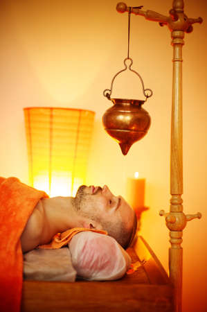 Man having a shirodhara massage in a salon photo