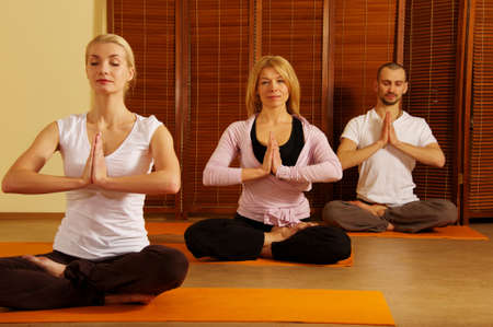 positions: Group of people doing yoga exercise Stock Photo