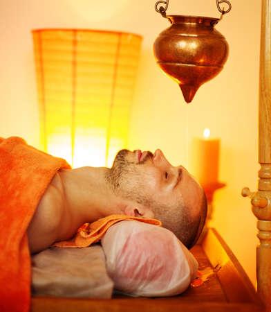 Man having a shirodhara massage in a salon photo