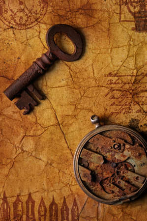 The old key with a gears on the textured paper Stock Photo - 9119274