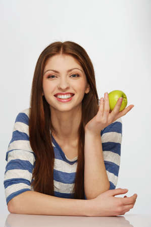 Beautiful brunette woman with a green apple photo