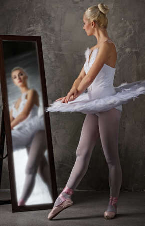 Beautiful ballet dancer near the mirror photo
