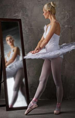 Beautiful ballet dancer near the mirror photo