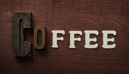 The word coffee written on wooden background photo
