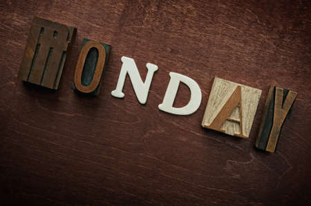 The word monday written on wooden background photo