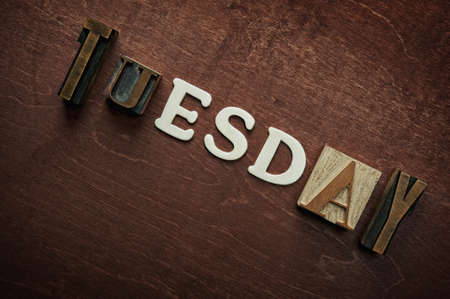 The word tuesday written on wooden background photo