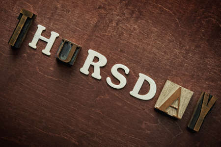 The word thursday written on wooden background photo