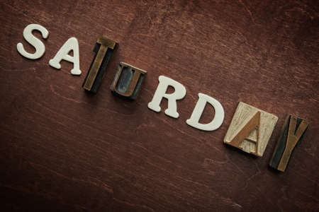 The word saturday written on wooden background photo