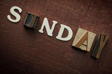 The word sunday written on wooden background photo