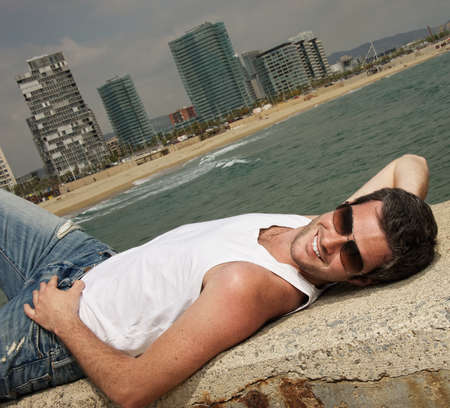 sexy male model: Handsome man relaxing near the sea