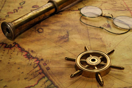 Steering wheel, glasses and spyglass on the old map photo