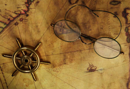 Glasses and sea wheel on the old map photo