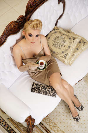 women holding cup: Beautiful woman drinking coffee in a luxury interior