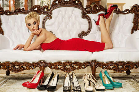 lying on couch: Beautiful glamorous woman looking at shoes