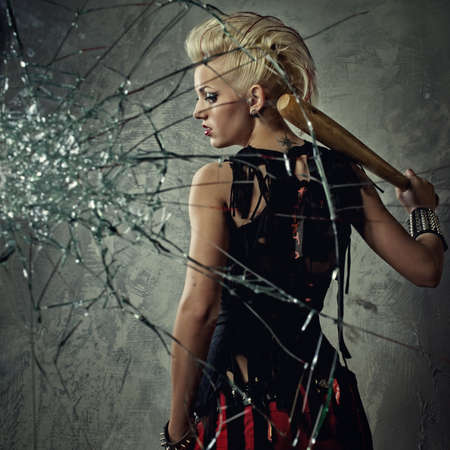 rebels: Punk girl with a bat behind broken glass Stock Photo