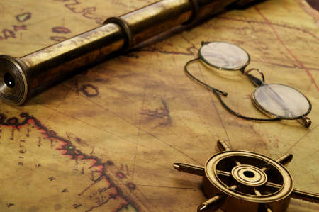 spyglass: Steering wheel, glasses and spyglass on the old map