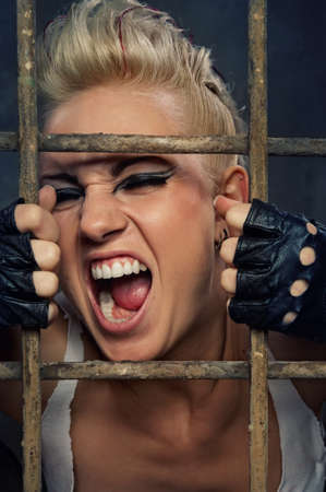 Punk girl screaming behind bars photo