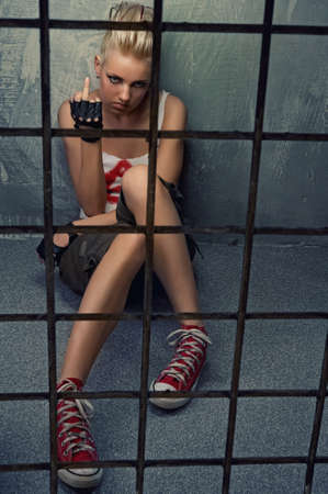 female prisoner: Punk girl showing middle finger behind bars Stock Photo