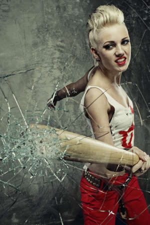 Punk girl broking a glass with a bat photo