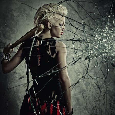 vidrio roto: Chica punk con un bate detr�s de vidrio roto Foto de archivo