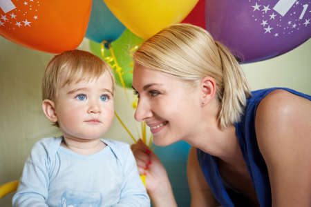 Happy mother with her baby celebrating birthday photo