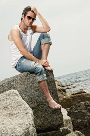 Handsome man sitting on a rock photo
