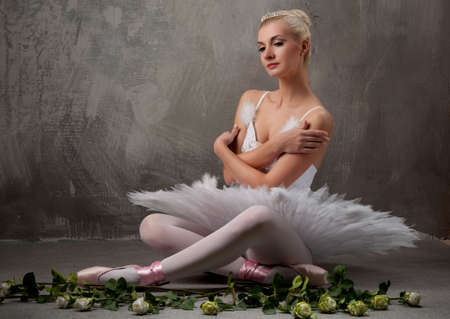 Beautiful ballet dancer with a white roses photo