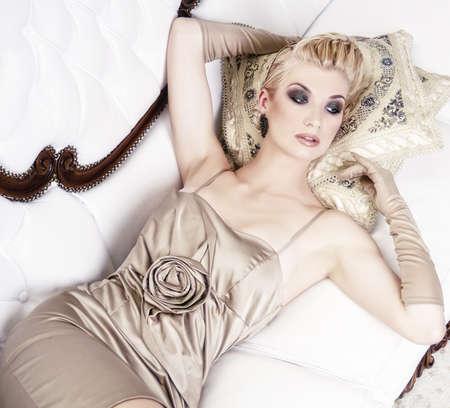 Beautiful blond woman lying on luxury sofa photo