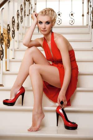 tacones rojos: Mujer rubia sentada en unas escaleras Foto de archivo