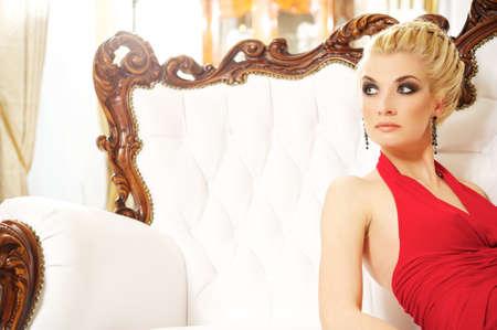 Blond woman sitting on luxury sofa photo
