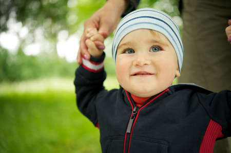 Smiling baby standing outdoors photo
