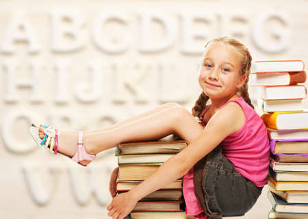 Little schoolgirl sitting on books  photo