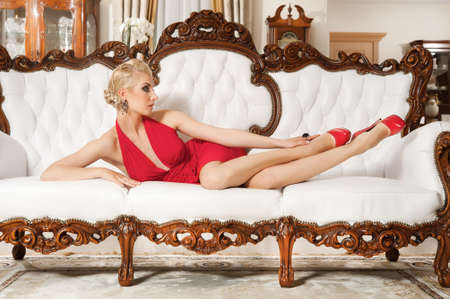 Lady in red dress  lying on luxury sofa photo