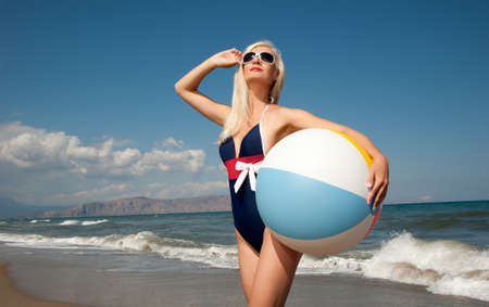 Pin up girl with a ball on a beach Stok Fotoğraf