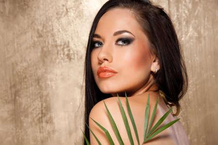Beautiful woman in bikini with tropical leaf photo