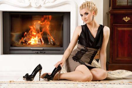 Blond lady near fireplace photo