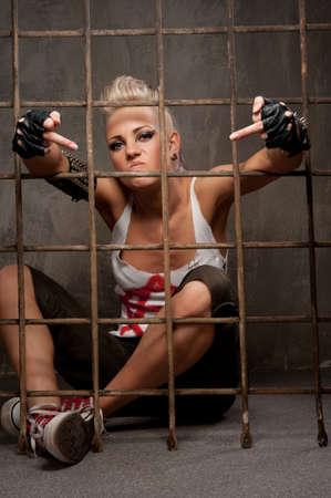 fuck: Punk girl behind bars showing rude gesture.