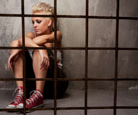 female prisoner: Punk girl behind bars.
