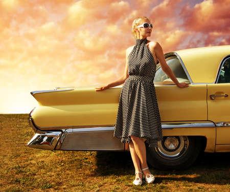 레트로 자동차 근처에 서있는 아름 다운 여자.