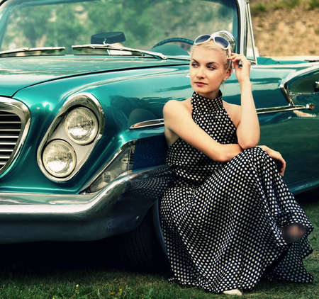 60s fashion: Beautiful lady sitting near retro convertible. Stock Photo