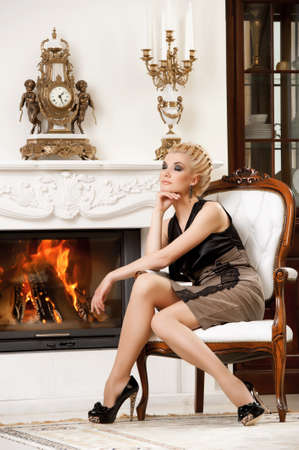 Blond lady near fireplace in a luxury interior photo