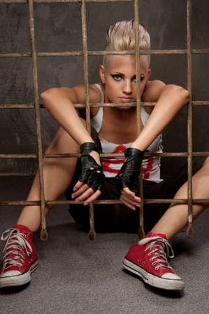 Punk girl behind bars. Stock Photo - 9999484