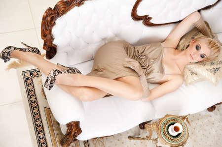 Blond lady lying on luxury sofa photo