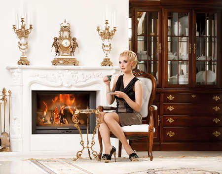Blond lady drinking coffee in luxury interior photo