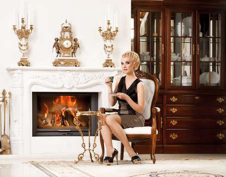 Blond lady drinking coffee in luxury interior photo