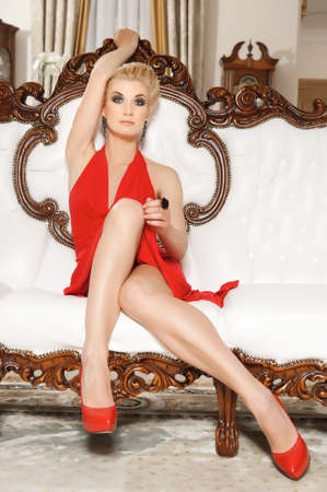 Lady in red dress on luxury sofa photo