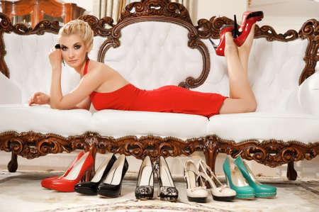 tacones rojos: Lady en vestido rojo tirado en el sofá de lujo Foto de archivo